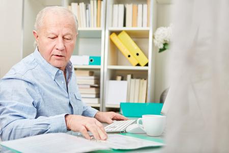 Business senior man making accounting at his desk Stock fotó