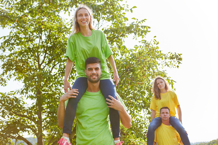 Young team makes piggyback riding in a workshop for teambuilding
