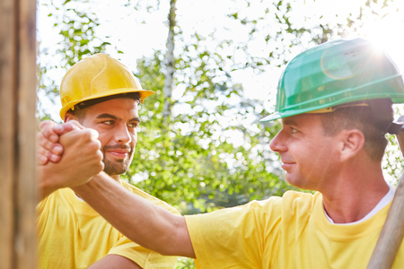 Two men as construction workers in house construction look forward to teamwork performance