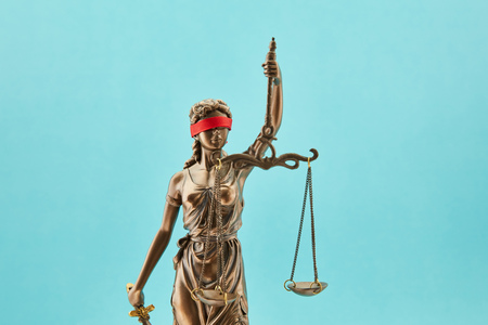 Justitia with blindfold as a justice concept in front of a blue background Stockfoto - 107163319