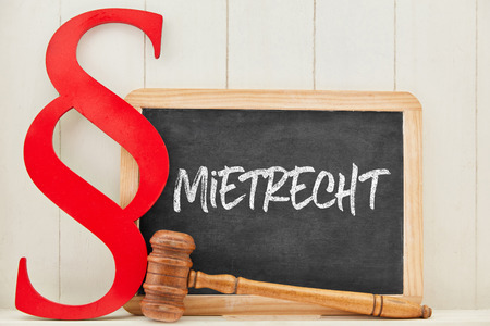 German word Mietrecht (tenancy law) as concept with law book paragraph next to a blackboard Banque d'images