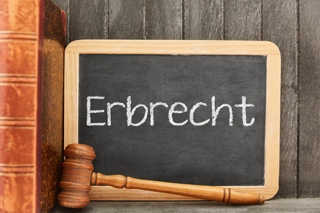 German word Erbrecht (Inheritance law) as concept on blackboard with gavel and law book