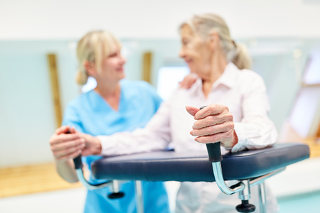 Senior woman as a patient in the rehab clinic while training with the walker