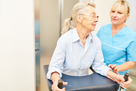 Physiotherapist helps an old disabled woman with rollator at the rehab clinic Stock Photo