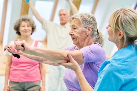 물리 치료 수석 여자는 트레이너의 도움으로 탄성 밴드로 운동을하고 있습니다