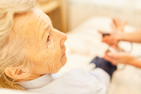 Senior woman as a patient taking blood pressure in nursing at nursing home