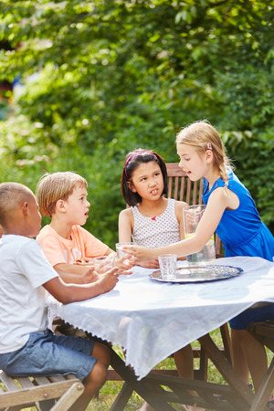 Interracial group of kids as friends drink water in garden for refreshment Standard-Bild