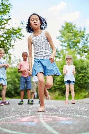 Girl in hopscotch competition in movement in summer
