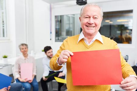 Senior man holds blank sign at creative idea brainstorming workshop