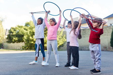 Student group is doing exercise with hoops in physical education in the schoolyard Stockfoto