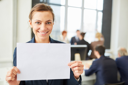 Happy woman smiling holds blank sign in business office