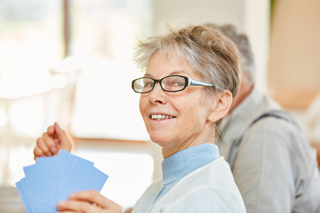 Vital senior woman enjoys playing cards with friends in retirement home