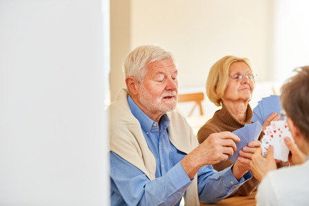 Group of seniors playing card games together in a retirement home or at home Stock Photo