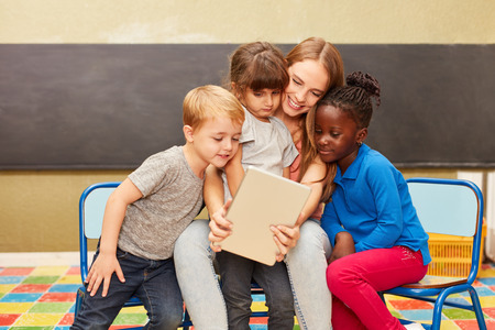 Kids and caregivers using tablet pc online have fun with social media in kindergarten