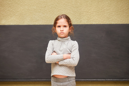 Schoolgirl stands with crossed arms in front of the blackboard in elementary school and gets annoyed