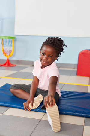 African girl in childrens gymnastics does an exercise to healthy stretching Zdjęcie Seryjne