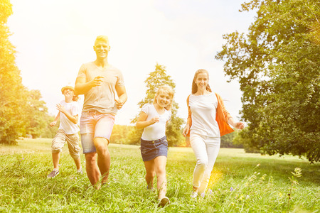 Happy family and kids are running together as a sport
