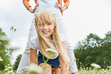 blond girl happily plays with her mother on a summer meadow
