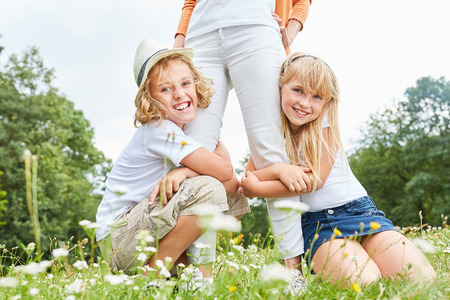 Brother and sister hug their mother in a meadow in summer