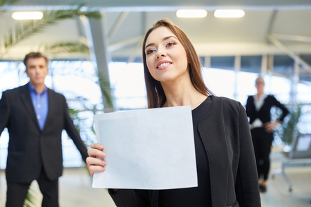 Business woman with a blank welcome sign at the airport terminal for a guest