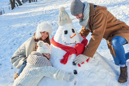 Family builds snowman together in winter in the park Stock Photo