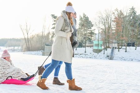 Family in winter taking a walk with their child while sled dragging Standard-Bild