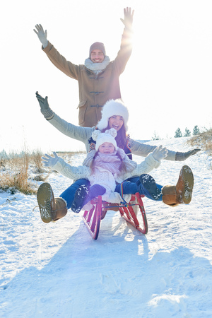La famille avec enthousiasme joue avec le traîneau en hiver Banque d'images