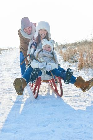 Famille s'amusant avec un toboggan en hiver dans la neige Banque d'images