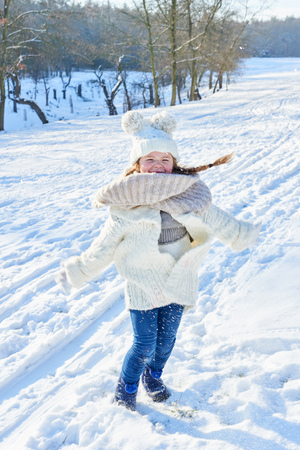Little girl in winter dancing and having fun in the snow Stock Photo