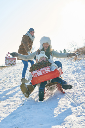 Mother and daughter as family in winter play toboggan with christmas gifts 免版税图像