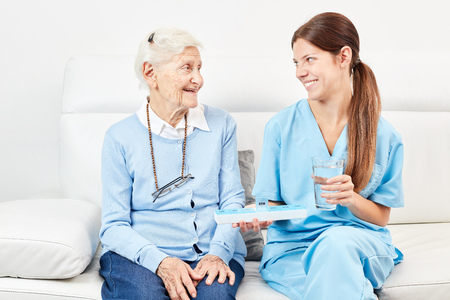 Female nurse gives senior citizen a drug in retirement home or at home Stock Photo