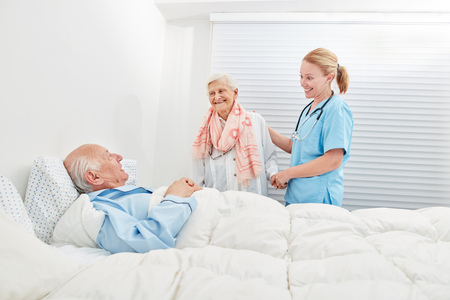 Senior as a patient in the hospital has a visit from his wife with the help of a nursing assistant Stock Photo