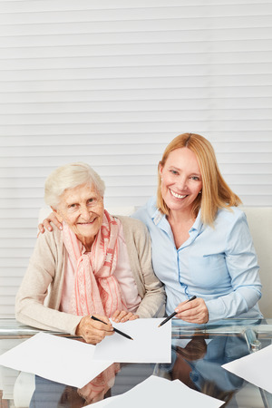 Woman helps elderly woman completing forms at home Reklamní fotografie