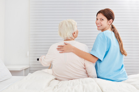 Caring nursing assistant helps senior citizen out of bed