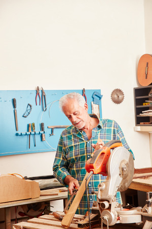 Senior carpenter works on new instrument's fingerboard Foto de archivo - 111530053