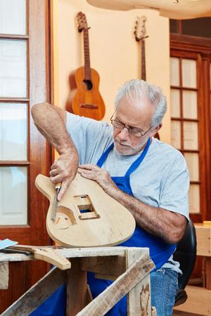 Craftsman makes manual work at luthier's workshop