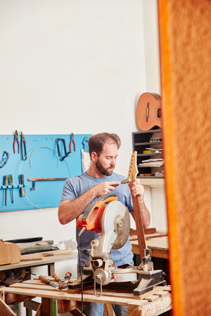 Man as craftsman builds new guitar at his workshop
