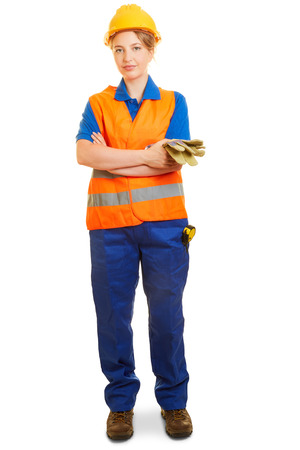 Jeune femme en tant qu'ouvrier du bâtiment en vêtements de protection avec casque et gilet de sécurité