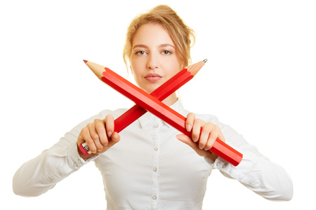 Woman holds two crossed big pins for defense and defense in the office