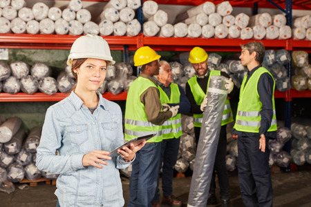 Woman as a logistics apprentice in the shipping center and warehouse worker in the background Banque d'images