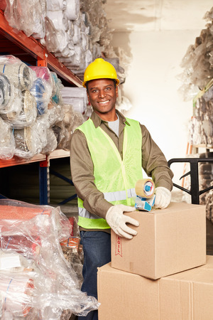 Young African worker as a packager by mail order with delivery Banque d'images