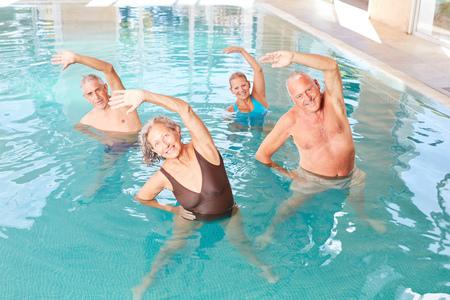 Gli anziani fanno stretching sano in un corso di acquagym
