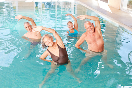Seniors make healthy stretching in a course for aquagym