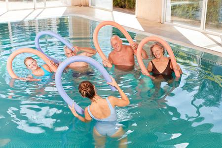 Gli anziani fanno insieme acquagym in piscina