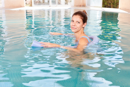 Young woman in swimming pool with swimming aid makes a hydrotherapy