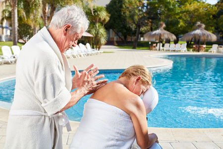 Senior woman gets back massage in wellness vacation by the swimming pool Archivio Fotografico