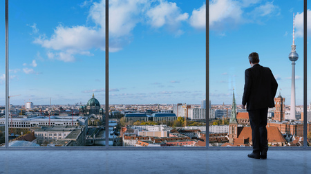 Business man lookig at Berlin city view from big office loft window (3D Rendering)