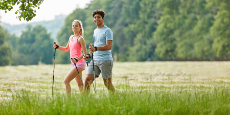 Young couple hiking in summer with walking sticks