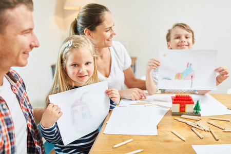 Children in family paint their dream home as a home wish before moving