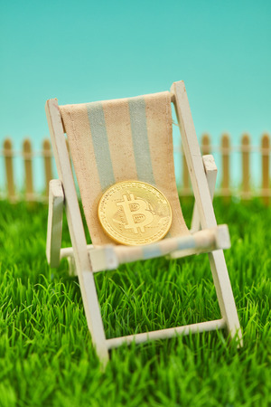 Golden Bitcoin coin lies in deckchair as a retirement concept 版權商用圖片